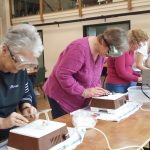ladies on the community stained glass project at Myddfai Hall learning to use grinding equipment
